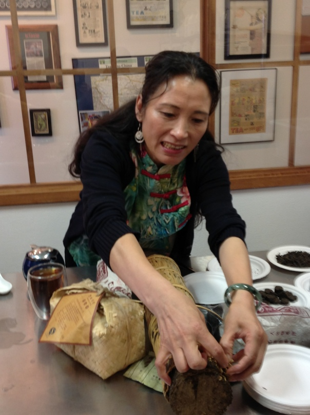 Ms Z tearing into a log of 100 Taels tea.  This is a compressed tea that is hand-wrapped with bamboo and then left to age.